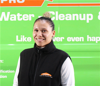 a woman in front of a green SERVPRO truck