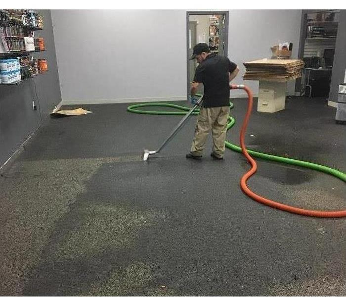 Technician extracting water from business after storm loss