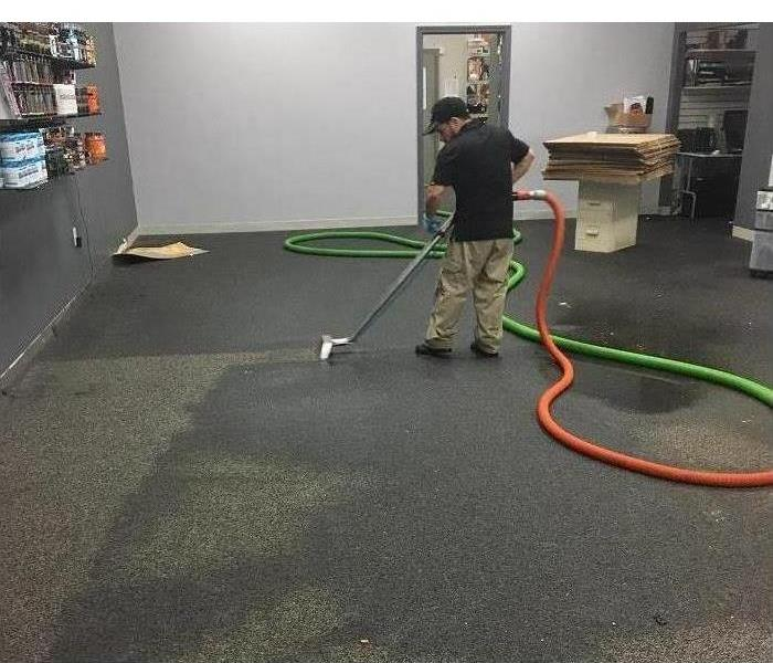 Man extracting water with vacuum on a commercial building